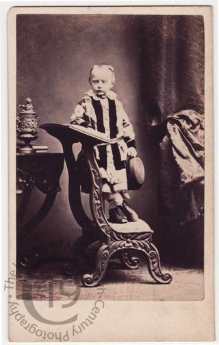 Boy standing on prie-dieu