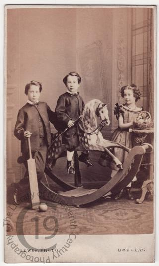 Three children with a rocking horse
