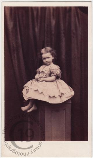 Barefooted child on pedestal