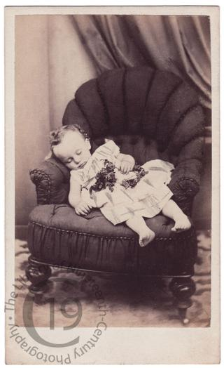 Bare-footed child on armchair