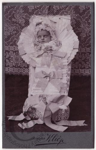 Baby in coffin with ribbons