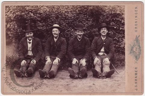 Four laughing men with cigars