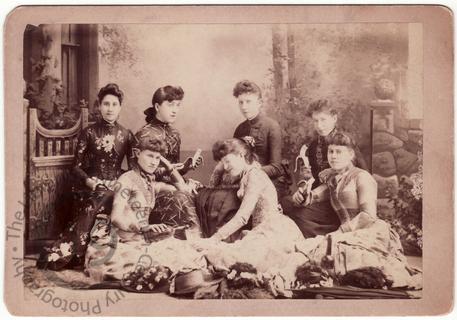 Seven young women eating bananas