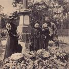 Three mourners at a graveside