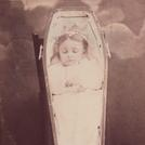 Girl in propped-up coffin