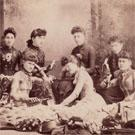 Seven young women eating bananas
